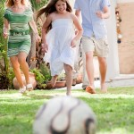 Happy family playing soccer and having fun